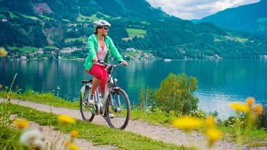 Frau radelt auf E-Bike am See entlang © Patrizia Tilly, stock.adobe.com