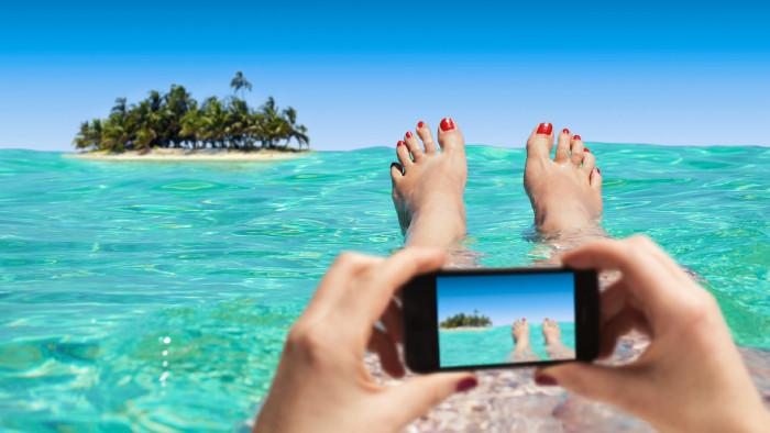 Frau macht Foto von Insel und ihren Füßen © TeamDaf, stock.adobe.com