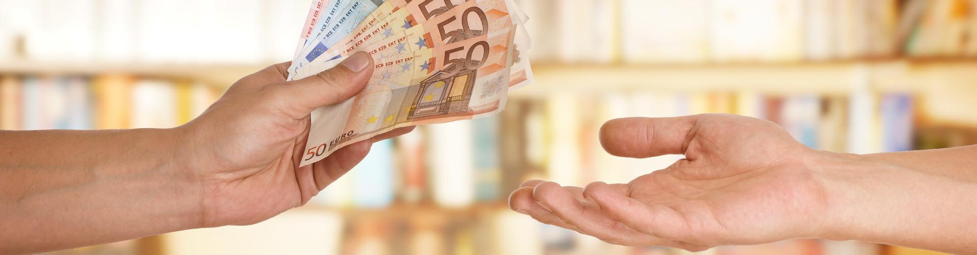 Eine Hand überreicht einer anderen Geld © underdogstudios, stock.adobe.com
