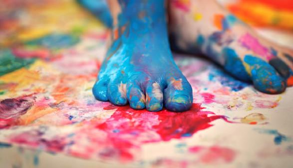Ein Kind malt mit seinen Füßen © Adobe Stock, kolinko_tanya