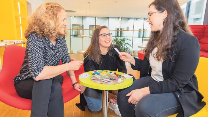 Drei junge Frauen probieren Spiele aus. © AKVbg