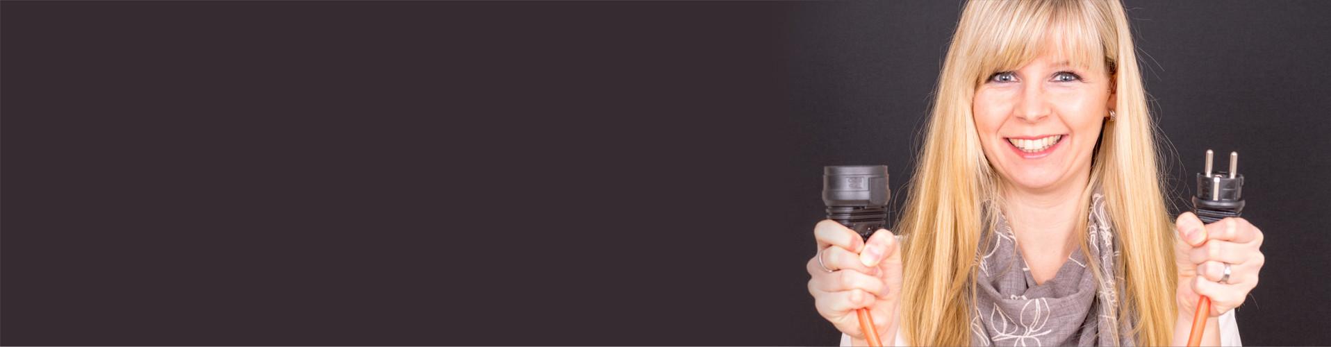 Frau steht vor dunklem Hintergrund und hält lächelnd zwei Enden eines Stromkabels in den Händen © usk75, stock.adobe.com
