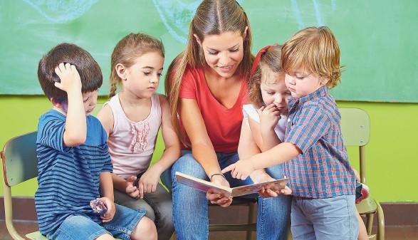 Erzieherin liest Buch mit Kindern  © Robert Kneschke, stock.adobe.com