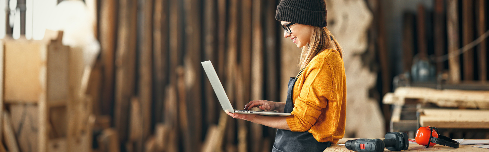 Frau mit Laptop in Montagehalle © Adobe Stock, JenkoAtaman