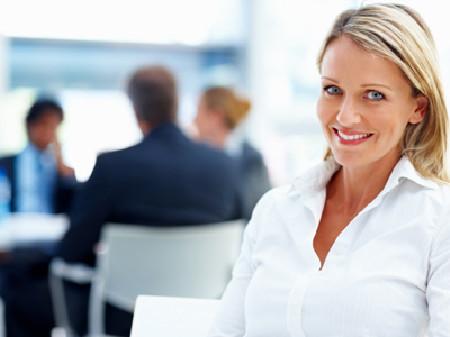 Blonde Frau lächelt. Im Hintergrund sitzen Menschen. © Yuri Arcurs, fotolia.com