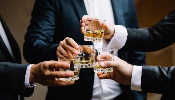 Männer in Anzügen, die mit Whiskey anstoßen © Adobe Stock, VAKSMANV