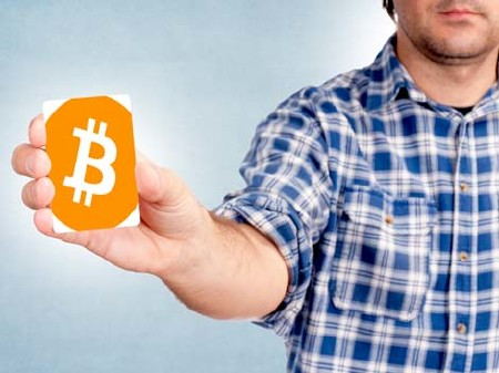 Mann hält Karte mit Bitcoin Symbol in der Hand © Family Business, stock.adobe.com