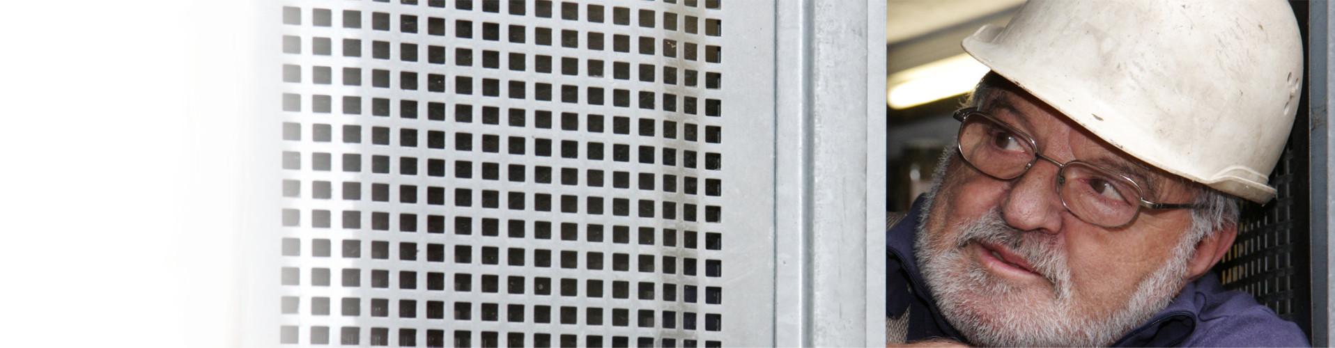Älterer Arbeiter blickt durch ein Wartungsgitter © Irina Fischer, stock.adobe.com