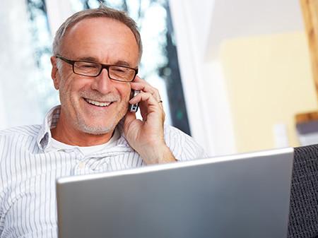 Mann mit Brille sitzt vor Laptop und telefoniert © Günter Menzl, Fotolia