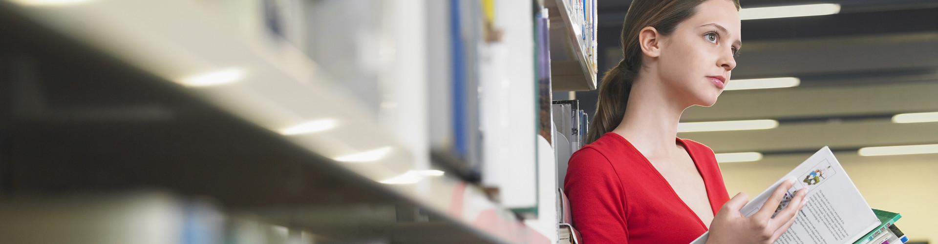 Junge Frau steht an ein Bücherregal gelehnt in der Bibliothek und hält dabei Lernunterlagen in der Hand. © biker3, stock.adobe.com