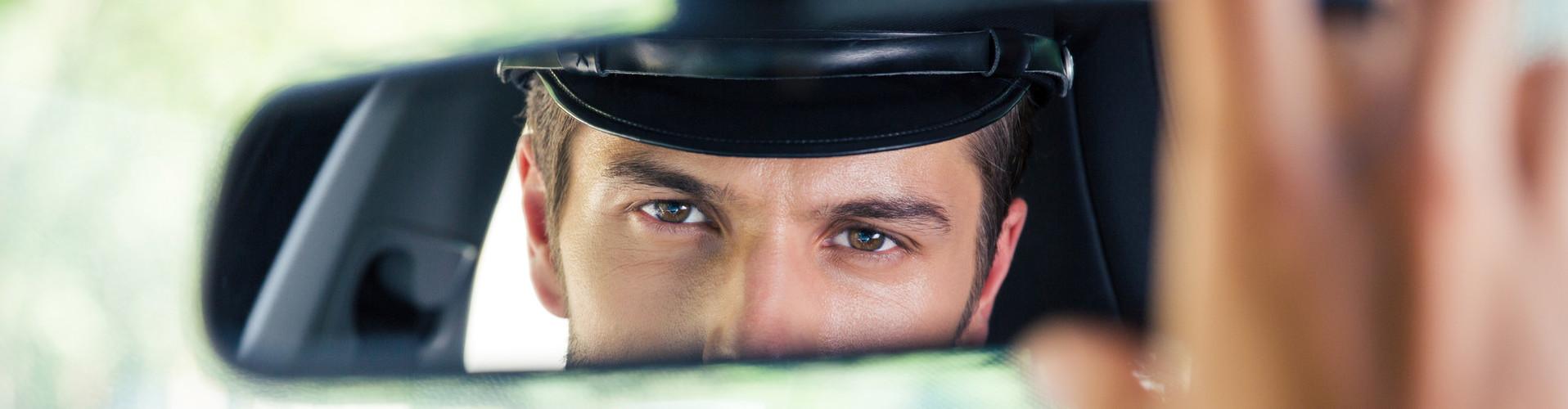 Man sieht das Gesicht eines Fahrers im Rückspiegel eines Wagens. Die rechte Hand stellt den Spiegel ein. © Drobot Dean, stock.adobe.com